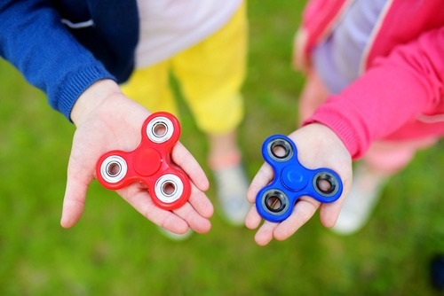 Children playing with fidget spinners